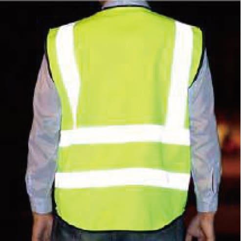 Homem vestindo colete amarelo com fitas refletivas expostas à luz